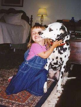 A girl in a pink shirt and blue jean suspenders is on her knees hugging a Dalmatian