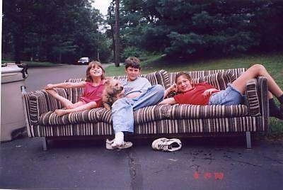 A boy and a tan Cairn Terrier are surrounded by two girls on a couch. The couch is outside in the street. The Cairn Terrier dog is looking to the right.