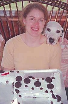 A Dalmatian has its head on the shoulder of a lady in a yellow shirt. There is a Dalmatian cake on a table in front of them