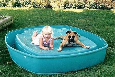 A blonde haired girl and a tan with white Boxer are laying out on an upside down kiddy pool.