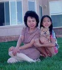A mother and a daughter are sitting in front of a house. A tan with white Pomeranian puppy is sitting in the daughters lap.