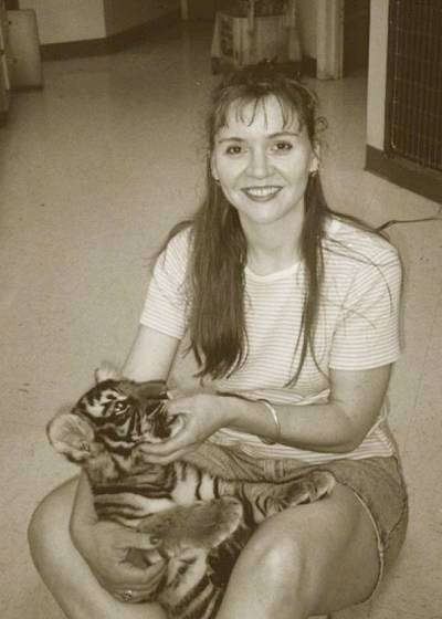 A black and white photo of a lady sitting on a carpeted floor with a Tiger Cub in her lap.