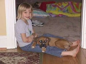 Amie sitting on the floor in a doorway with Allie the Boxer laying on her lap
