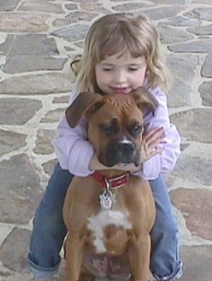 Sara hugging the back of Allie the Boxer on the stone porch