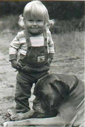 A black and white photo of a blonde toddler standing next to a Boxer that is laying down outside