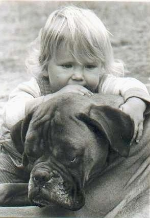 Close up - A black and white photo of a blonde toddler laying across the head of a Boxer dog outside in the dirt.