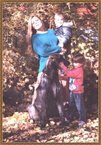 An Irish Wolfhound is sitting in leaves and looking at a childs face. There is a lady in a blue sweater behind them holding a baby.