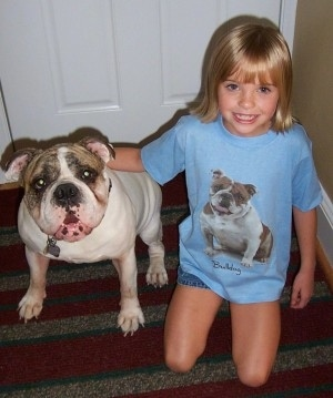 Spike the Bulldog sitting in front of a door next to Amie who is wearing a bulldog shirt