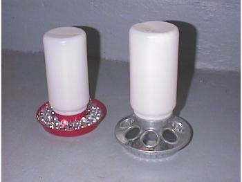 A water feeder with clear marbles in it and a food feeder.