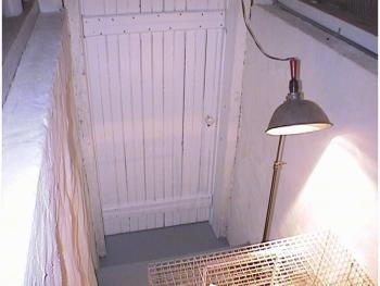 A heat lamp is beaming down on a white cage.