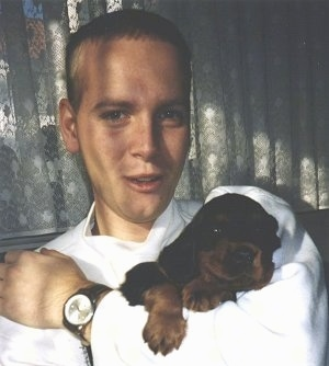 A black and tan Gordon Setter puppy is being held in the arm of a teenage boy wearing a white shirt and a watch.