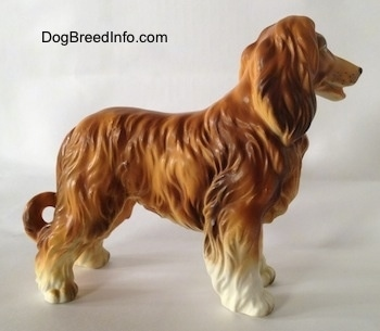 The right side of a brown with white Vintage porcelain Lefton Japan Afghan Hound dog figurine with a lot of texture for the long coat. It is holding its tail down low.