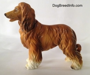 The left side of a brown with black and white Vintage porcelain Lefton Japan Afghan Hound dog figurine. The dog has a long snout with painted dots on it to be the wiskers.
