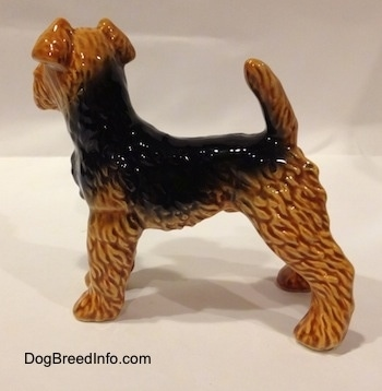 The left side of a shiny black and brown Vintage Airedale Terrier dog West Germany Goebel figurine with its tail up high over its back.