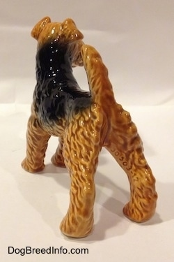 The back left side of a black and brown Vintage Airedale Terrier dog West Germany Goebel figurine. Its back legs are set wide apart.