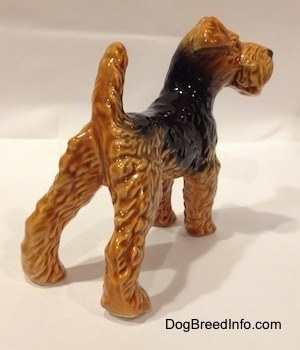 The back right side of a black and brown Vintage Airedale Terrier dog West Germany Goebel figurine with its back legs set wide apart and its tail up in the air.
