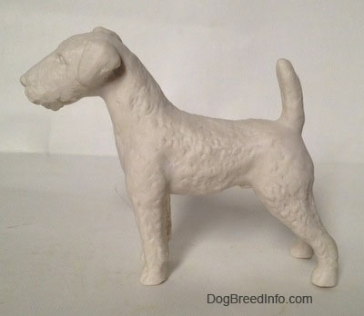 The left side of a white bisque porcelain Airedale Terrier dog figurine that is unglazed and not shiny.