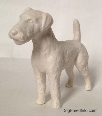The front left side of a white bisque porcelain Airedale Terrier dog figurine that is unglazed. The dog has straight legs and a straight muzzle.