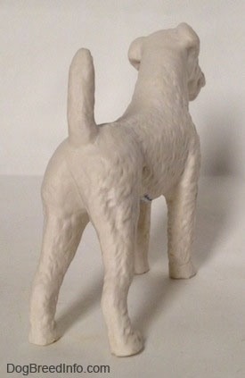 The back right side of a white bisque porcelain Airedale Terrier dog figurine that is unglazed. The dogs bak legs are straight and the tail is up high in the air.