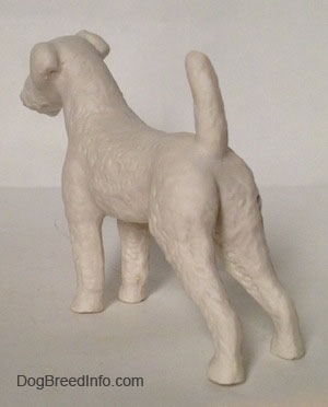 The back left side of a white bisque porcelain Airedale Terrier dog figurine that is unglazed. The dog is leaning forward.