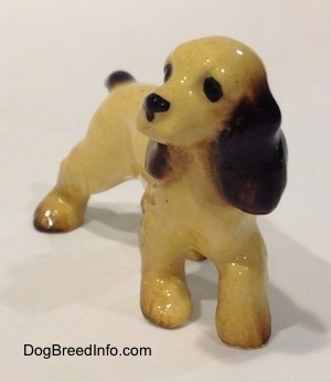 A tan with black and brown Cocker Spaniel ceramic figurine is looking to the left.