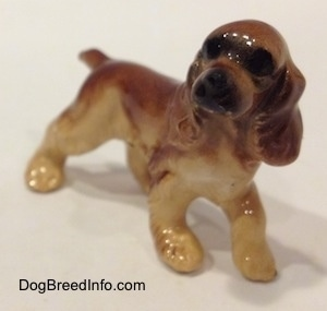 The front right side of a brown and tan ceramic Cocker Spaniel figurine. It has light hair brushings.