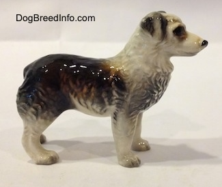 The right side of a black and white Australian Shepherd figurine. The figurine has detailed eyes.