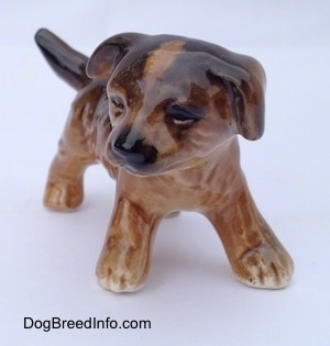 The front right side of a brown and black porcelain Aussie puppy figurine. The figurine has fine paw details.