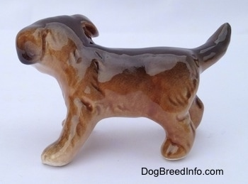 The left side of a brown and black porcelain Aussie puppy figurine. The figurine is very glossy.