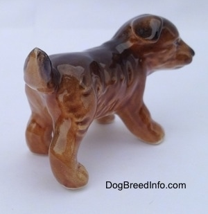The back right side of a brown and black porcelain Aussie puppy figurine. It has a small amount of hair detail.