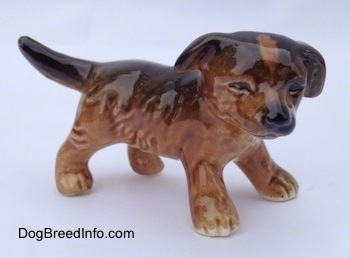 The right side of a brown and black porcelain Aussie puppy figurine. The eyes are very detailed on the figurine.