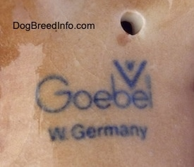 Close up - The underside of a brown and black porcelain Aussie puppy figurine. The logo of Goebel W. Germany is on the underside of the figurine.