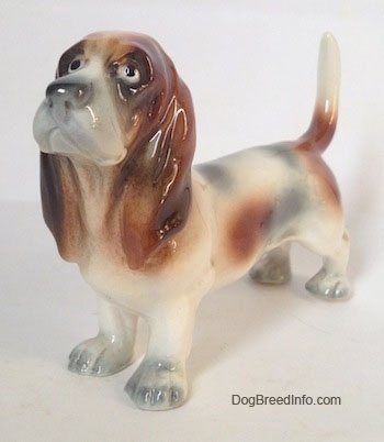 The front left side of a white with black and red Basset Hound figurine. The eyes of the figurine are black circles.