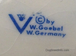 Close up - The underside of a white with black and red Basset Hound figurine has the words - © by W.Goebel W. Germany - on it.