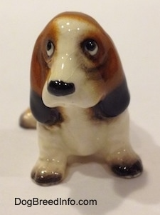 A black, brown and white ceramic Basset Hound figurine. The figurine shaping is not precise.
