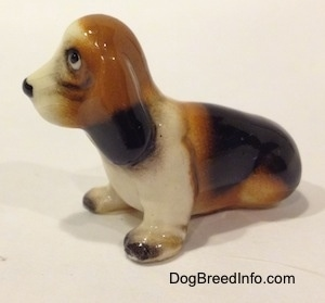 The left side of a black, brown and white ceramic Basset Hound figurine. The ears of the figurine are attached to the neck.