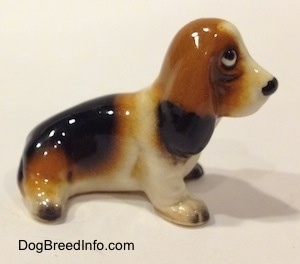 The right side of a black, brown and white ceramic Basset Hound figurine. The figurine lacks fine details.