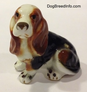The front left side of a brown, black and white ceramic Basset Hound figurine. The figurine has light face details.
