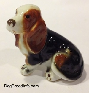 The left side of a brown, black and white ceramic Basset Hound figurine. The figurine is very glossy.