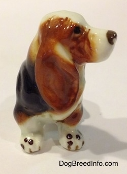 A brown, black and white ceramic Basset Hound figurine. The nose of the figurine has some fine details.