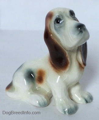 The right side of a white with black and red ceramic Basset Hound figurine. The figurine has black circles for eyes.