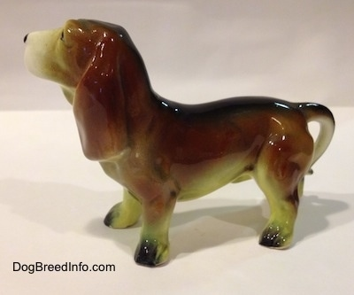 The left side of a brown with white and black ceramic Basset Hound figurine. The figurine has great ear details.