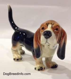 The front right side of a black with white and brown Basset Hound figurine. The figurine is very glossy.