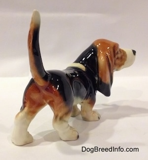 The back right side of a black with white and brown Basset Hound figurine. The figurine has great painting details.