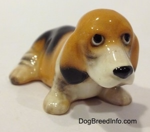 The front right side of a tan and black with white ceramic Basset Hound figurine. The eyes of the figurine are black circles.