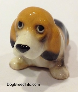 The front left side of a tan and black with white ceramic Basset Hound figurine. The figurine is glossy.