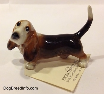 The left side of a black and brown with white Basset Hound figurine. The figurine has black circles for eyes.