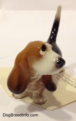 A black and brown with white Basset Hound figurine. The figurine has sad eyes.