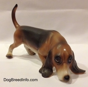 The front right side of a brown and black with white porcelain Basset Hound figurine that is sniffing. The face of the figurine is highly detailed.