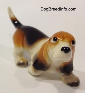 The front right side of a black, tan and white ceramic Basset Hound figurine. The figurine does not have a mouth.